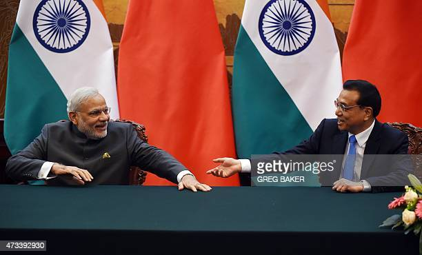 India's Prime Minister Narendra Modi chats with Chinese Premier Li Keqiang during a signing ceremony in the Great Hall of the People in Beijing on...