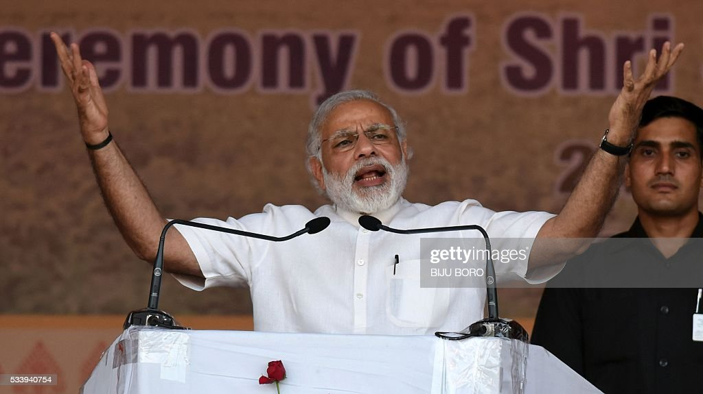 India's Prime Minister Narendra Modi gestures as he addresses the audience during the swearing-in ceremony of Sarbananda Sonowal as Chief Minister of the north-eastern state of Assam in Guwahati on May 24, 2016. India's ruling Bharatiya Janata Party claimed victory in Assam elections, marking the first time the Hindu nationalist party has won control of a state in the India's restive northeast. / AFP / Biju BORO