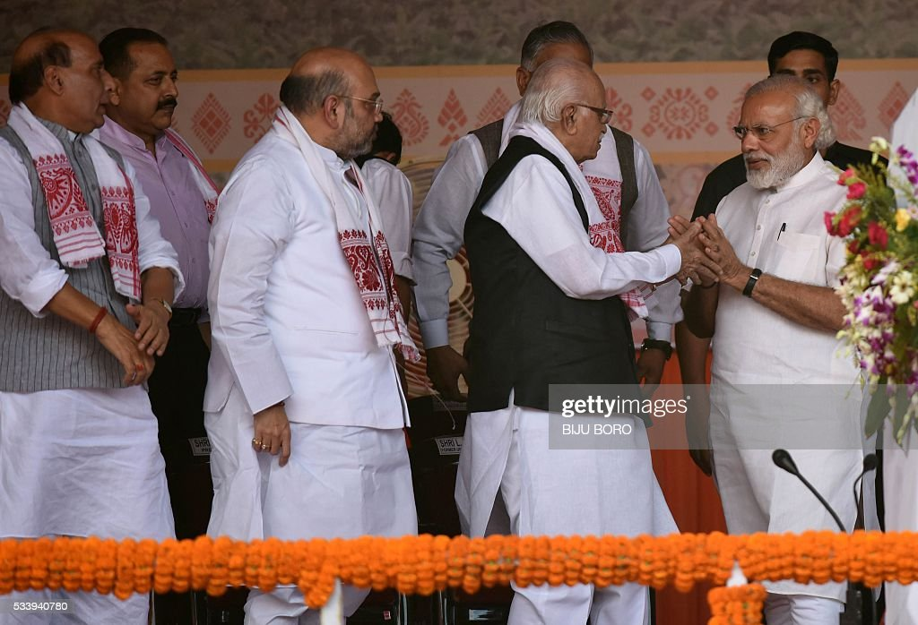 India's Prime Minister Narendra Modi(R) greets Bharatiya Janata Party (BJP) senior leader Lal Krishna Advani(2R) and other BJP leaders during the swearing-in ceremony of Sarbananda Sonowal as Chief Minister of the north-eastern state of Assam in Guwahati on May 24, 2016. India's ruling Bharatiya Janata Party claimed victory in Assam elections, marking the first time the Hindu nationalist party has won control of a state in the India's restive northeast. / AFP / Biju BORO