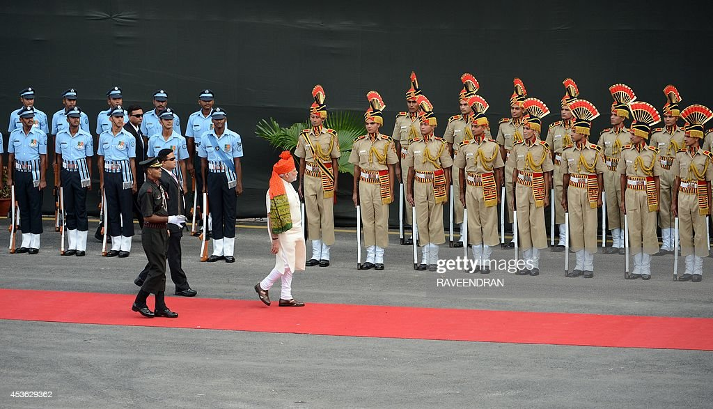 India's Prime Minister Narendra Modi (C) inspects a guard of honour to mark the country's 68th Independence Day at the Red Fort in New Delhi on August 15, 2014. Modi condemned a spate of rapes as a source of shame for India and urged an end to communal violence on August 15 as he vowed to improve the lives of the nation's poor in his first Independence Day speech. AFP PHOTO / RAVEENDRAN