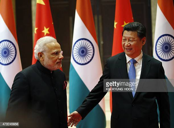 India's Prime Minister Narendra Modi is shown the way to a meeting room by China's President Xi Jinping ahead of their meeting in Xian in China's...