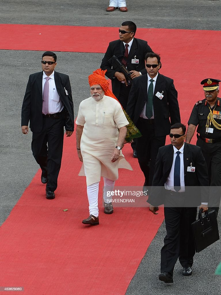 India's Prime Minister Narendra Modi (C) is surrounded by security after inspecting a guard of honour to mark the country's 68th Independence Day at the Red Fort in New Delhi on August 15, 2014. Modi condemned a spate of rapes as a source of shame for India and urged an end to communal violence on August 15 as he vowed to improve the lives of the nation's poor in his first Independence Day speech. AFP PHOTO / RAVEENDRAN