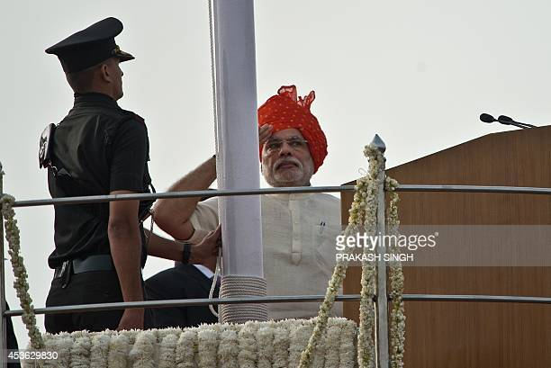 India's Prime Minister Narendra Modi salutes while unfluring the national flag at the Red Fort to mark the country's 68th Independence Day in New...