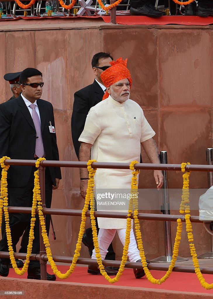 India's Prime Minister Narendra Modi (R) walks with security officials as he arrives to deliver a speech from the ramparts of the Red Fort in New Delhi on August 15, 2014, to mark the country's 68th Independence Day. Modi condemned a spate of rapes as a source of shame for India and urged an end to communal violence on August 15 as he vowed to improve the lives of the nation's poor in his first Independence Day speech. AFP PHOTO / RAVEENDRAN