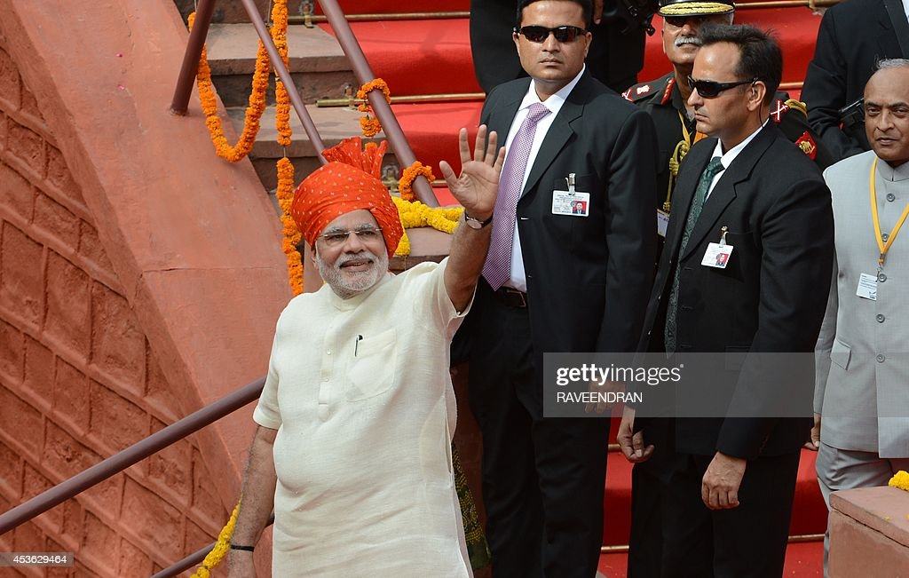 India's Prime Minister Narendra Modi (L) waves after delivering a speech from the ramparts of the Red Fort in New Delhi on August 15, 2014, to mark the country's 68th Independence Day. Modi condemned a spate of rapes as a source of shame for India and urged an end to communal violence on August 15 as he vowed to improve the lives of the nation's poor in his first Independence Day speech.