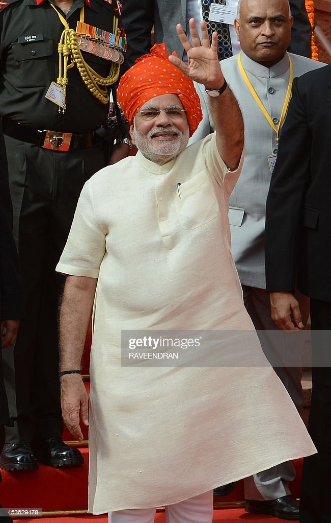 India's Prime Minister Narendra Modi (C) waves after delivering a speech from the ramparts of the Red Fort in New Delhi on August 15, 2014, to mark the country's 68th Independence Day. Modi condemned a spate of rapes as a source of shame for India and urged an end to communal violence on August 15 as he vowed to improve the lives of the nation's poor in his first Independence Day speech. AFP PHOTO / RAVEENDRAN