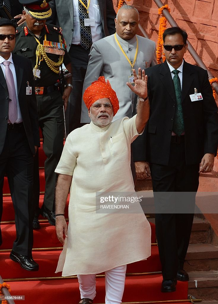 India's Prime Minister Narendra Modi (C) waves after delivering a speech from the ramparts of the Red Fort in New Delhi on August 15, 2014, to mark the country's 68th Independence Day. Modi condemned a spate of rapes as a source of shame for India and urged an end to communal violence on August 15 as he vowed to improve the lives of the nation's poor in his first Independence Day speech.