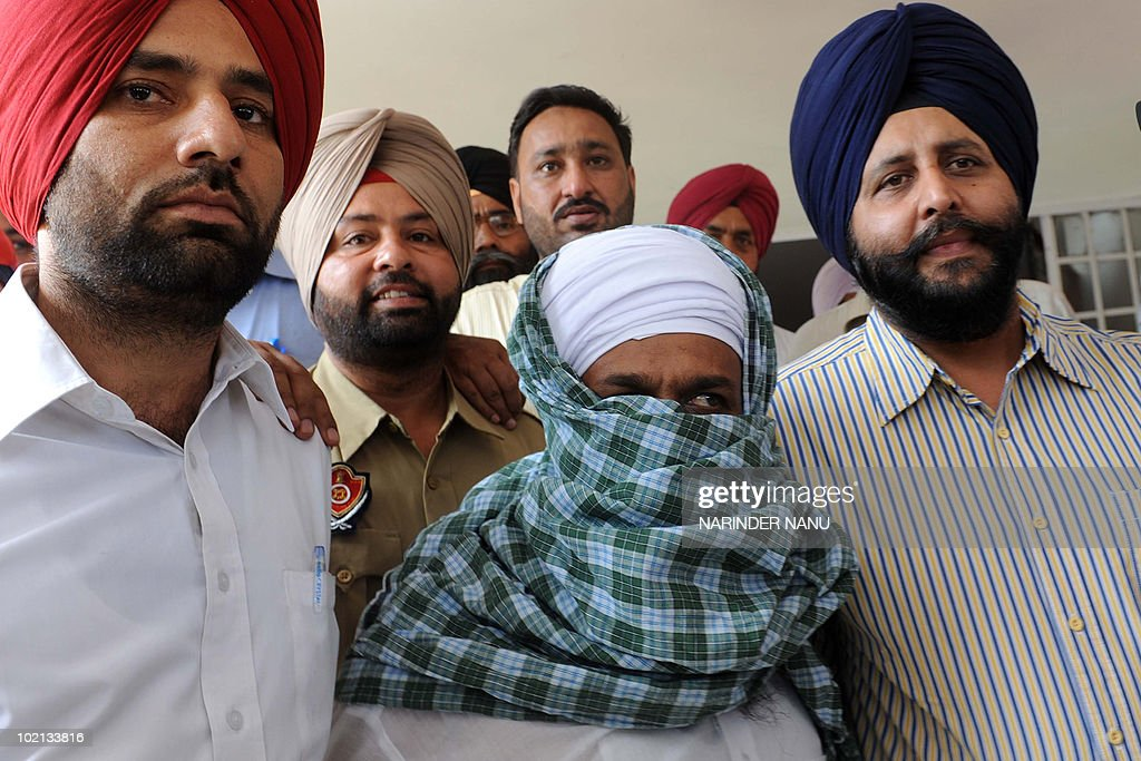 India's Punjab state Special Narcotics Cell police escorts suspected militant Sukhdev Singh Sukha (C) to an appearance in court in Amritsar on June 16,2010. Officials arrested one militant Sukhdev Singh and recovered one AK-74 rifle along with 4 magazines and 190 cartridges, one sub-machine gun along with 2 magazines and 100 cartridges, two 30 bore pistols along with 4 magazines and 80 cartridges (in addition to one pistol shown above) and 1.4 Kg RDX, believed to have been smuggled into the country from neighbouring Pakistan.