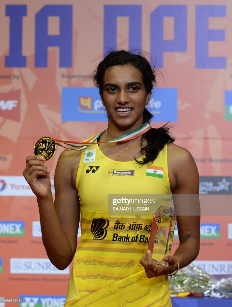 India s Pusarla V Sindhu poses with a gold medal after winning