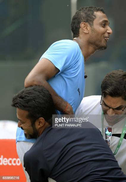 India's Ramkumar Ramanathan celebrates with team mate Leander Peas after winning the Davis Cup singles tennis match against New Zealand's Finn...