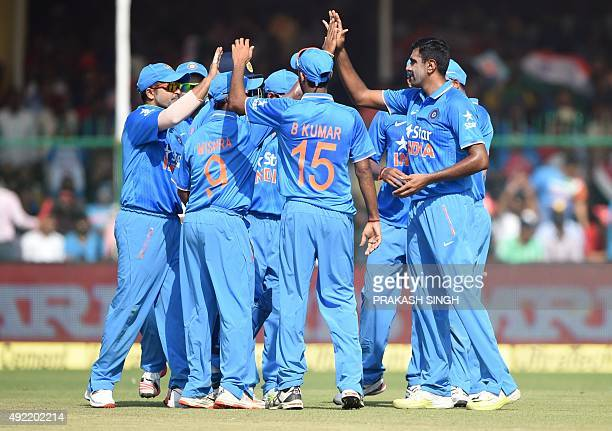 India's Ravichandran Ashwin celebrates with teammates after his dismissal of unseen South Africa's Quinton de Kock during the first one day...
