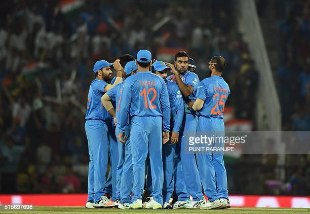 India's Ravichandran Ashwin celebrates with teammates after taking the wicket of New Zealand batsman Martin Guptill during the World T20 cricket...