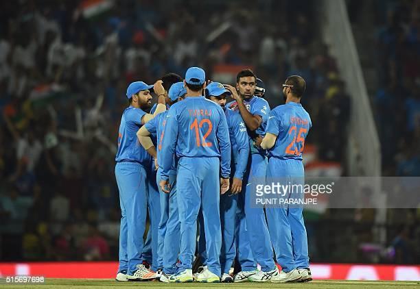 India's Ravichandran Ashwin celebrates with teammates after taking the wicket of New Zealand batsman Martin Guptill during the World T20 cricket...