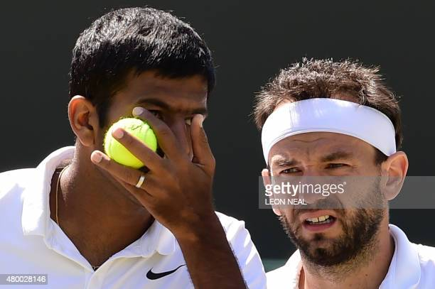 India's Rohan Bopanna and his partner Romania's Florin Mergea talk between points against Netherlands' JeanJulien Rojer and Romania's Horia Tecau...