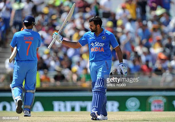 India's Rohit Sharma raises his bat after reaching 150 runs during the oneday international cricket match between India and Australia in Perth on...
