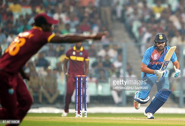 India's Rohit Sharmais watched by West Indies's captain Darren Sammy as he plays a shot during a warmup match between India and West Indies for the...
