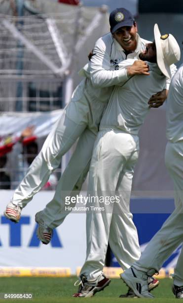 India's Sachin Tendulkar celebrates with team mate Harbhajan Singh after taking a catch to dismiss England's captain Andrew Flintoff in the third and...