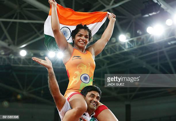 India's Sakshi Malik celebrates after winning against Kirghyzstan's Aisuluu Tynybekova in their women's 58kg freestyle bronze medal match on August...