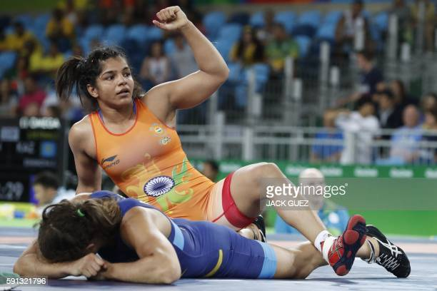 India's Sakshi Malik celebrates during her fight againt Sweden's Malin Johanna Mattsson in their women's 58kg freestyle qualification match on August...