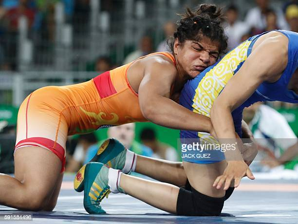 India's Sakshi Malik wrestles with Kirghyzstan's Aisuluu Tynybekova in their women's 58kg freestyle bronze medal match on August 17 during the...