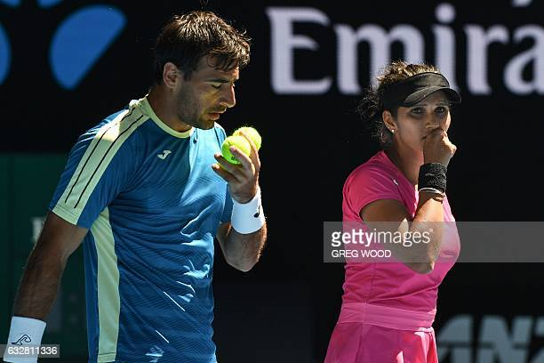 India's Sania Mirza and Croatia's Ivan Dodig speak between points during their mixed doubles semifinal match against Australia's Sam Groth and...