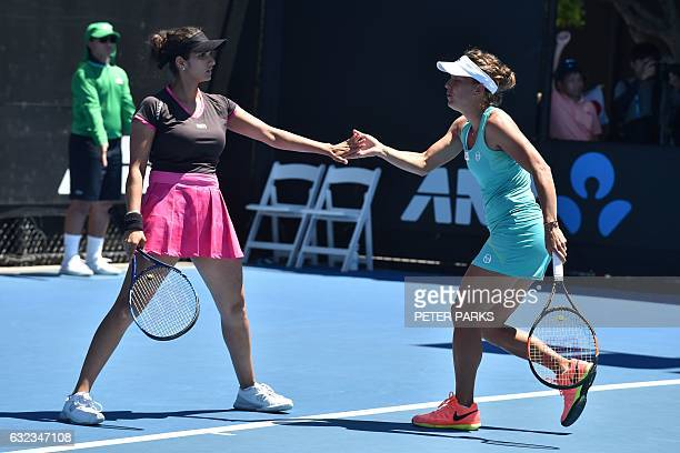 India's Sania Mirza gestures with partner Czech Republic's Barbora Strycova during their women's doubles third round match against Japan's Eri Hozumi...