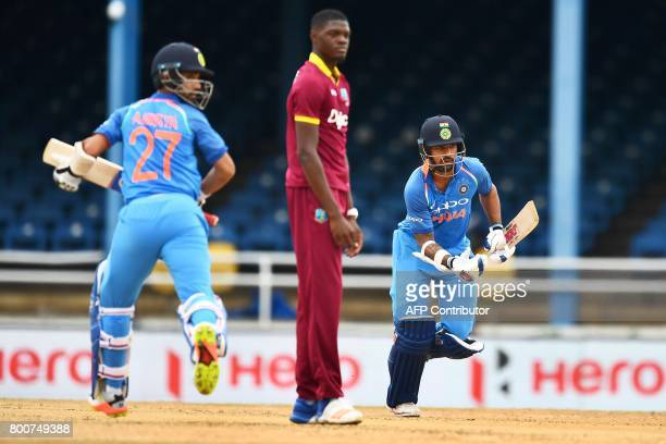 India's Shikhar Dhawan and Ajinkya Rahane takes a run as West Indies' Alzarri Joseph looks on during the second One Day International match between...