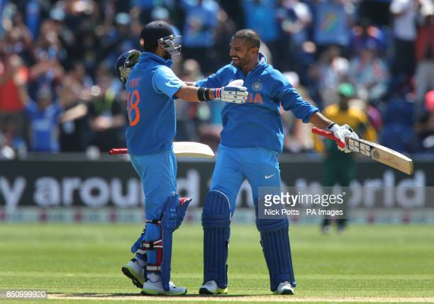 India's Shikhar Dhawan celebrates his 100 not out with Virat Kohli during game against South Africa on opening day of the ICC Champions Trophy The...
