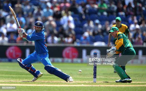 India's Shikhar Dhawan hots out during his innings of 114 against South Africa watched by wicketkeeper AB De Villiers on the opening day of the ICC...