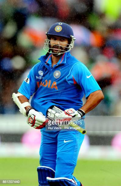 India's Shikhar Dhawan protects his bat after another rain delay during the ICC Champions Trophy match at Edgbaston Birmingham