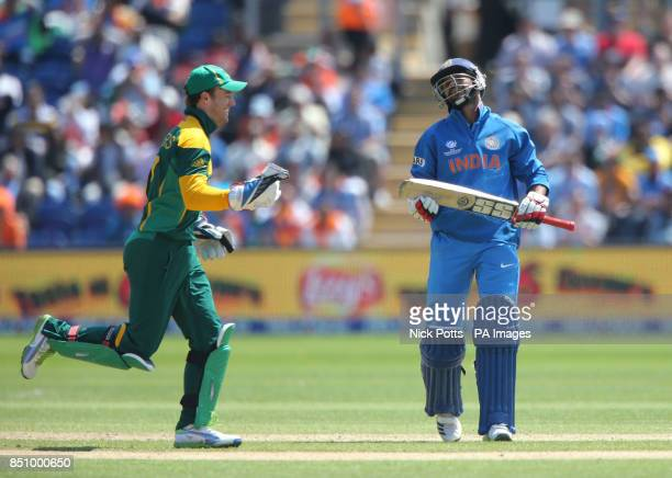 India's Shikhar Dhawan shows his dejection after he was out for 114 as South Africa captain wicketkeeper AB De Villiers celebrates on opening day of...