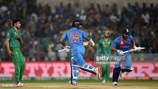 India's Shikhar Dhawanand Rohit Sharmarun between the wickets as Pakistan's Mohammad Amirlooks on during the World T20 cricket tournament match...