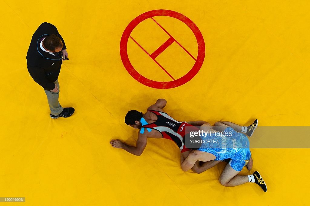 India's Sushil Kumar wrestles Japan's Tatsuhiro Yonemitsu in their Men's 66kg Freestyle gold medal match on August 12 2012 during the wrestling event...
