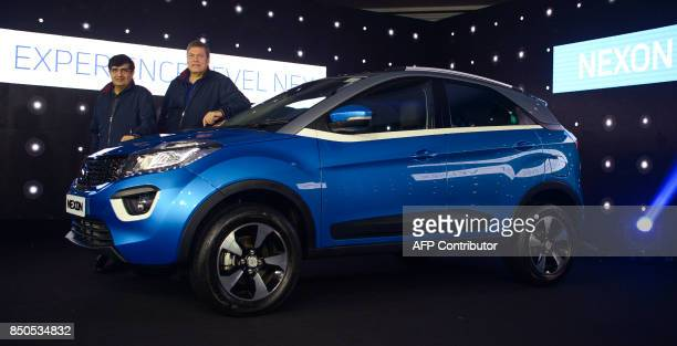 India's Tata Motors Chief Executive Officer Guenter Butschek and President of Passenger Vehicle Business Unit Mayank Pareek pose with the new 'Nexon'...