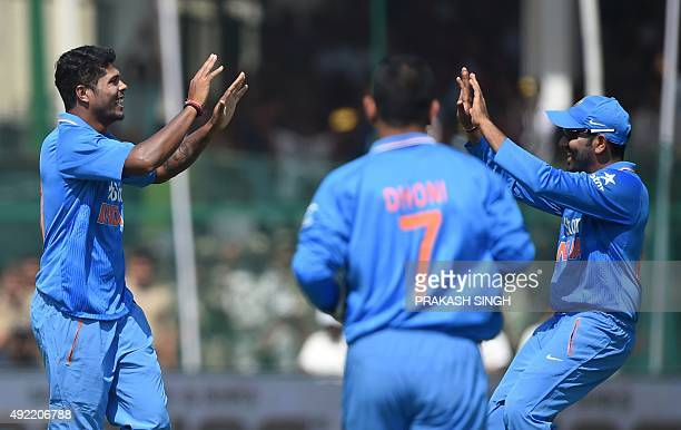 India's Umesh Yadav celebrates his dismissal of unseen South Africa's Faf du Plessis with teammates captain Mahendra Singh Dhoni and India's Rohit...