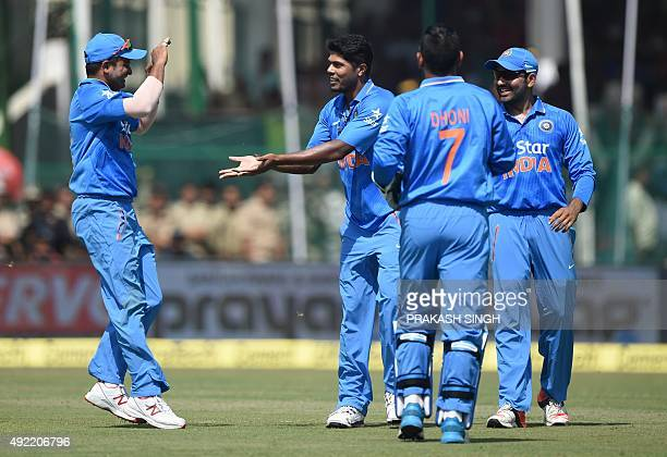 India's Umesh Yadav celebrates his dismissal of unseen South Africa's Faf du Plessis with teammates Suresh Raina captain Mahendra Singh Dhoni and...