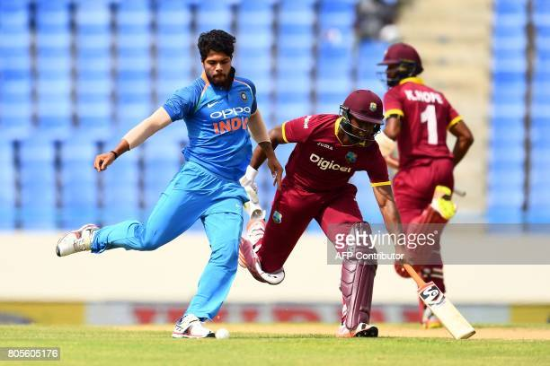 India's Umesh Yadav kicks the ball in an unsuccessful attempt to run out West Indies' Evin Lewis during the fourth One Day International match...
