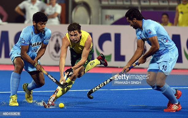 India's Uthappa Sannuvanda and Dharamvir Singh block Australia's Flynn Ogilvie during their Hero Hockey Champions Trophy 2014 match for 3rd 4th...