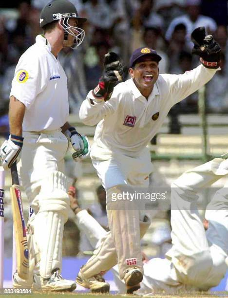 India's Venkatsai Laxman holds the ball after making a catch to dismiss Australian batsman Justin Langer as Indian wicketkeeper Sameer Dighe...