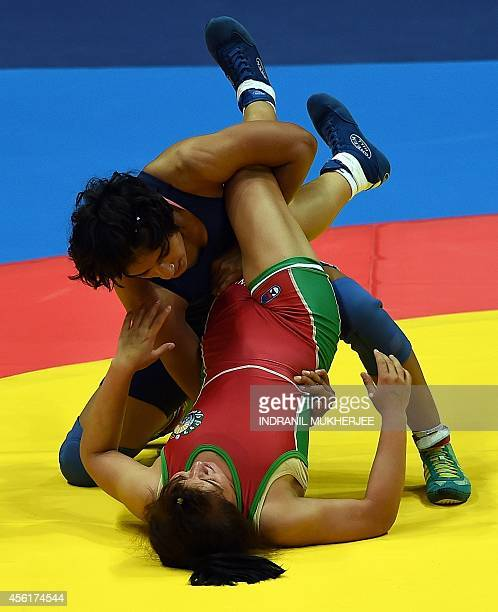 India's Vinesh pins down Uzbekistan's Dauletbike Yakhshimuratova during the women's freestyle wrestling 48 kg event of the 2014 Asian Games at the...
