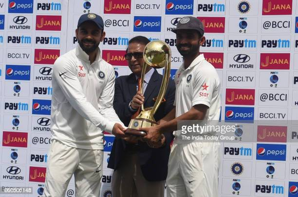 India's Virat Kohli and Ajinkya Rahane receive the trophy from the former Indian cricket player Sunil Gavaskar after winning the series during the...