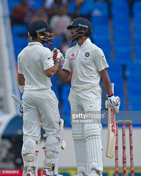 India's Virat Kohli and Shikhar Dhawan celebrates Kohli's 50 runs during day one of the cricket Test match between West Indies and India July 21 2016...