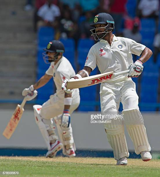 India's Virat Kohli and Shikhar Dhawan run during day one of the cricket Test match between West Indies and India July 21 2016 at Sir Vivian Richards...