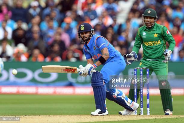 India's Virat Kohli bats as Pakistan wicketkeeper Sarfraz Ahmed looks on during the ICC Champions trophy match between India and Pakistan at...