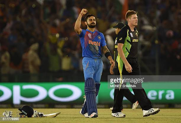 India's Virat Kohli celebrates after victory as Australia's James Faulkner looks on in the World T20 cricket tournament match between India and...