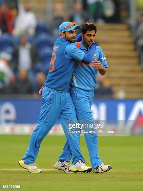 India's Virat Kohli congratulates team mate Bhuvaneshwar Kumar after he takes the wicket of Sri Lanka's Kusal Perera during the ICC Champions Trophy...