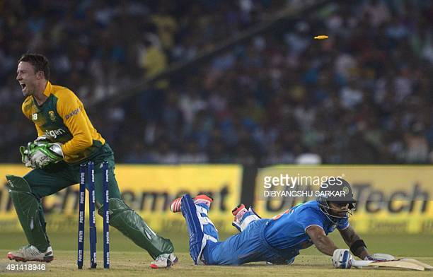 India's Virat Kohli dive to reach the crease as South Africa's AB de Villiers celebrates after running him out during the second T20 cricket match...