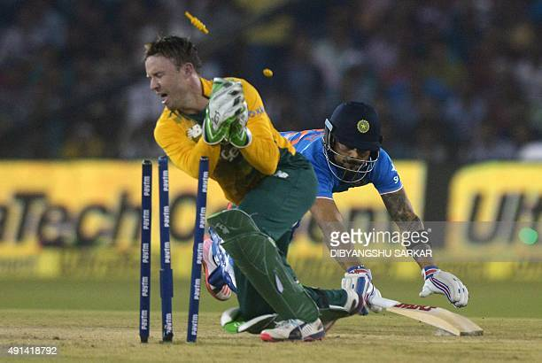 India's Virat Kohli dives to reach the crease as South Africa's AB de Villiers runs him out during the second T20 cricket match between India and...