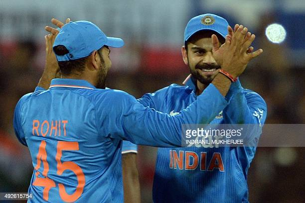 India's Virat Kohli is congratulated by teammate Rohit Sharma after taking a catch for the dismissal of South Africa's captain AB de Villiers during...