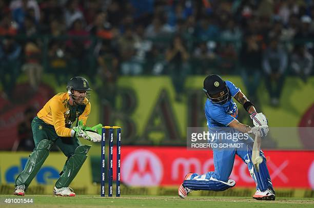 India's Virat Kohli plays a shot as South Africa's wicketkeeper AB de Villiers looks on during the first T20 cricket match between India and South...